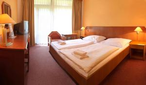 A bed or beds in a room at Hotel Harmonie
