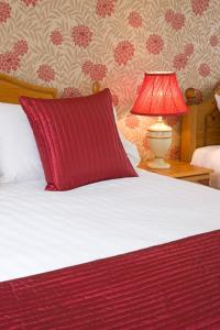 A bed or beds in a room at Lochnell Arms Hotel