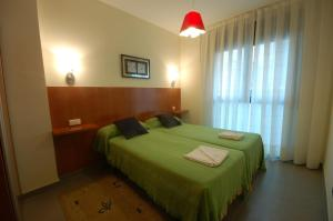 A bed or beds in a room at Hotel Led Sitges
