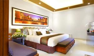 A bed or beds in a room at The Banyumas Suite Villa Legian