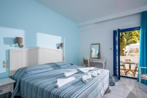 A bed or beds in a room at Hotel Hara Ilios Village
