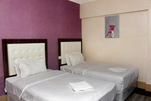 A bed or beds in a room at Delmon Hotel Apartments