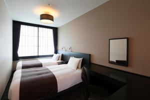 A bed or beds in a room at Kyoto Tower Hotel
