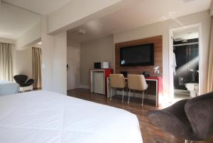 Uma TV ou centro de entretenimento em Ez Aclimação Hotel