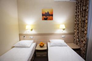 A bed or beds in a room at Apelsin Hotel on Komsomolskaya