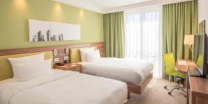 A bed or beds in a room at Hampton by Hilton Nürnberg City Center