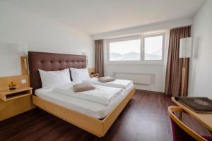 A bed or beds in a room at Seerausch Swiss Quality Hotel