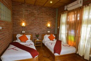 A bed or beds in a room at Teak Wood Hotel