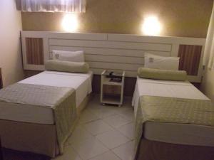 A bed or beds in a room at Pousada Pérola Do Morro