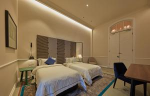 A bed or beds in a room at The Edison George Town