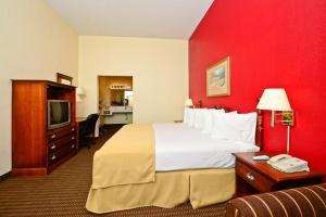 A bed or beds in a room at Manchester Heritage Inn & Suites