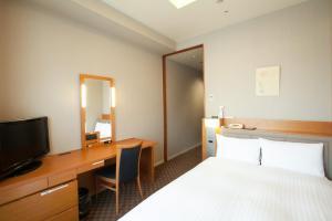 A bed or beds in a room at KKR Hotel Umeda