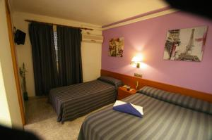 A bed or beds in a room at Hostal Apolo Trece