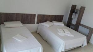 Cama ou camas em um quarto em Pousada Peruíbe Ametista