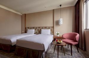 A bed or beds in a room at Orange Hotel - Wenhua, Chiayi