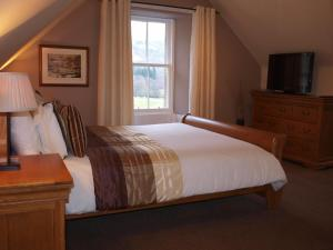 A bed or beds in a room at The Coach House Hotel