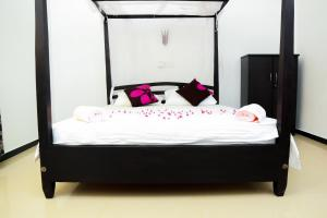 A bed or beds in a room at Anila Beach Inn
