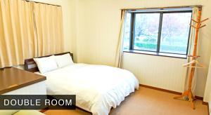 Tempat tidur dalam kamar di Bakpak Kyoto Hostel