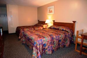 A bed or beds in a room at Twilite Motel & RV Park