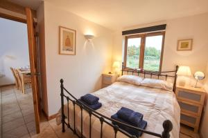 A bed or beds in a room at Barn Cottages at Lacock