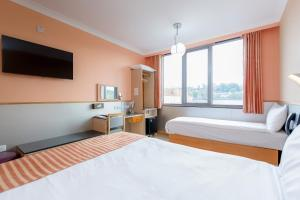 A bed or beds in a room at Eurotraveller Hotel - Premier - Harrow