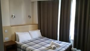 A bed or beds in a room at Lynden Court Hotel