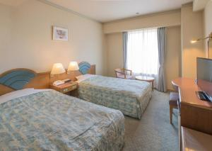 A bed or beds in a room at Hotel Crescent Asahikawa