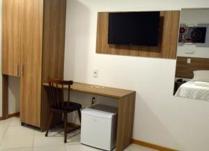 Una televisión o centro de entretenimiento en Mar de Canasvieiras Hotel e Eventos