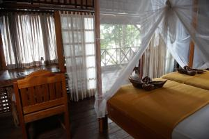 A bed or beds in a room at Raja Ampat Dive Resort