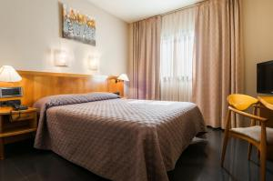 A bed or beds in a room at Hotel Ruta de Europa