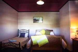 A bed or beds in a room at Boorowa Hotel