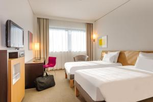 A bed or beds in a room at Novotel München Airport
