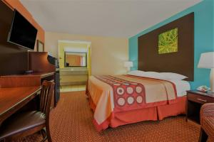 A bed or beds in a room at Super 8 by Wyndham Tulsa