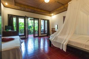 A bed or beds in a room at Tropical Bali Hotel