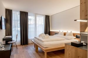 A bed or beds in a room at die berge lifestyle-hotel sölden