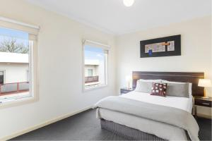 A bed or beds in a room at Hawthorn Gardens Serviced Apartments