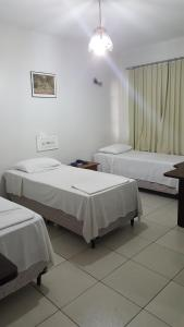 A bed or beds in a room at Veneza Plaza Hotel