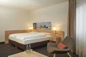 Ein Bett oder Betten in einem Zimmer der Unterkunft H+ Hotel Darmstadt