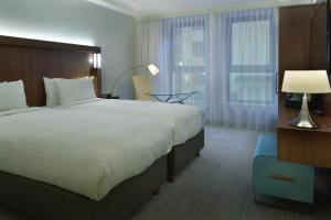 A bed or beds in a room at Courtyard by Marriott Brussels EU