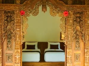 A bed or beds in a room at Eden House Ubud
