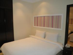 A bed or beds in a room at Marina Royal Hotel Suite