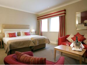 A bed or beds in a room at Donnington Valley Hotel, Golf & Spa