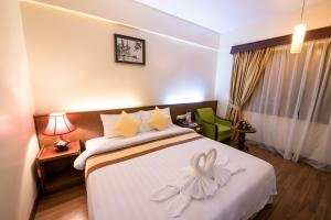 A bed or beds in a room at Ohana Phnom Penh Palace Hotel