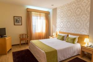 A bed or beds in a room at Hotel Eurosol Alcanena