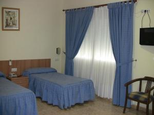 A bed or beds in a room at Hotel Los Hermanos