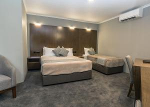 A bed or beds in a room at Bankstown Motel 10