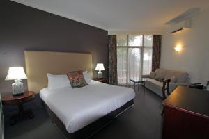 A bed or beds in a room at Mercure Resort Hunter Valley Gardens