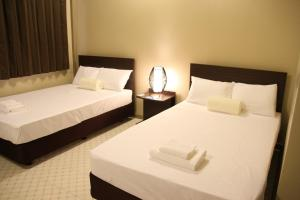 A bed or beds in a room at DW Motel