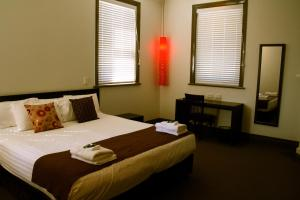 A bed or beds in a room at The Burwood Inn