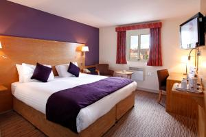 A bed or beds in a room at Mercure Wigan Oak Hotel